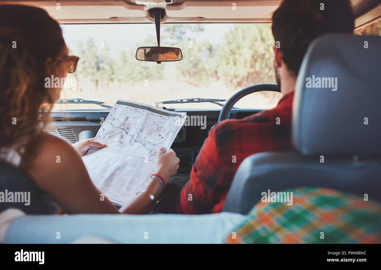 Rear view shot of couple driving on country road. Woman holding a route map with man driving the car. Couple on - Stock Image