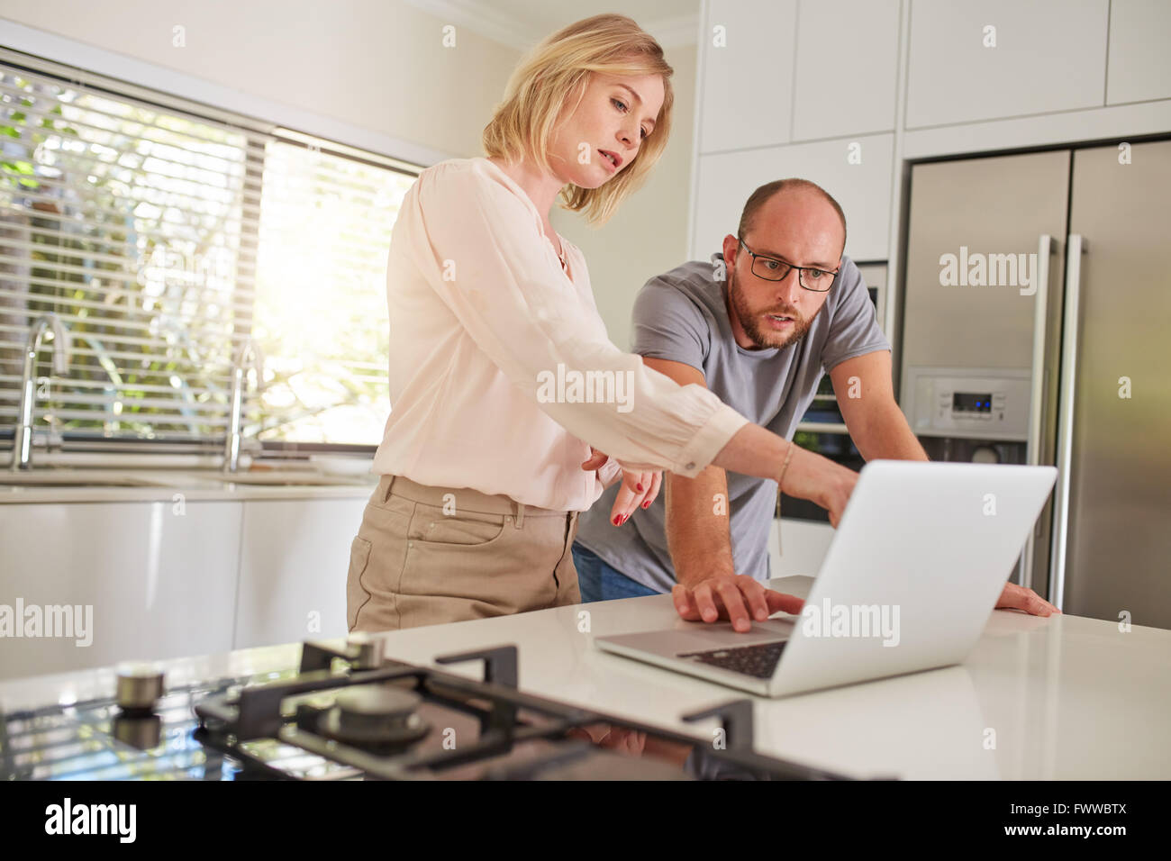 Portrait of mature couple working together on a laptop in the kitchen. Couple standing by the kitchen counter, with - Stock Image