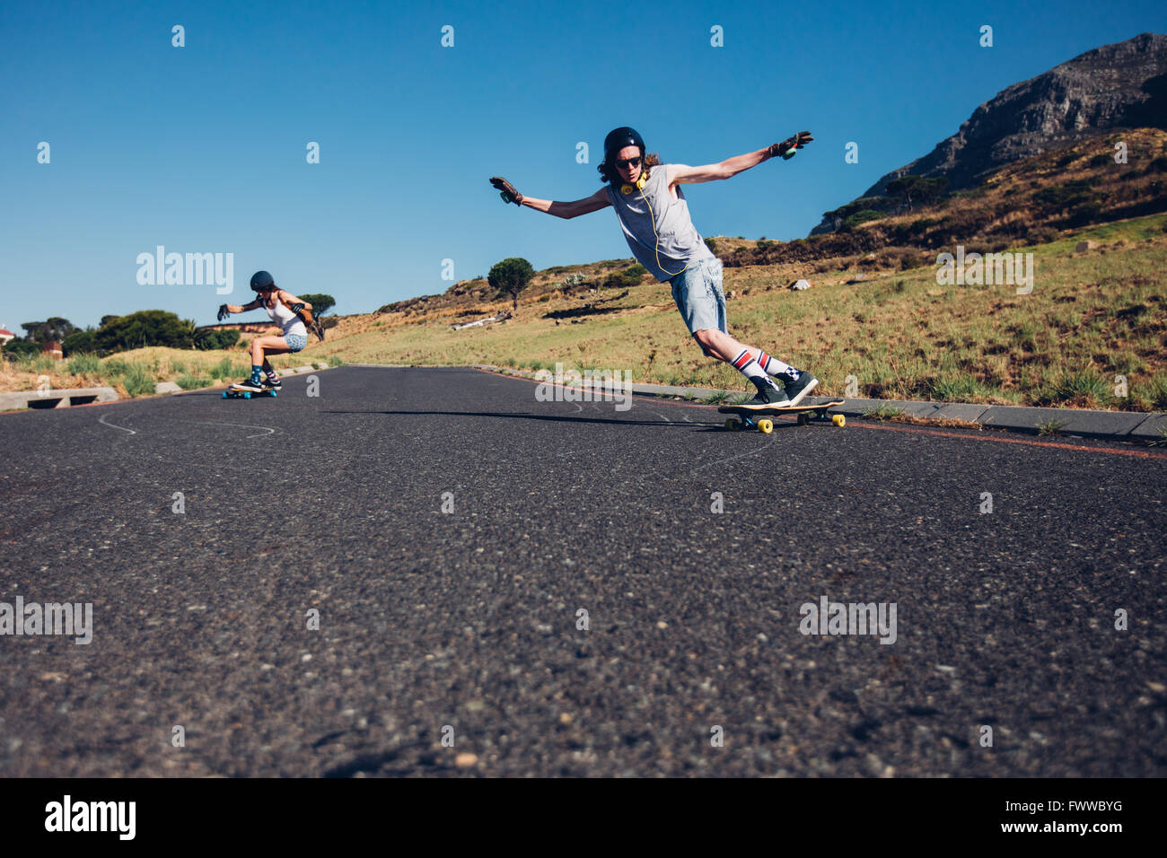 Young man and woman skateboarding on the rural road. Young couple enjoying skating on the road. - Stock Image