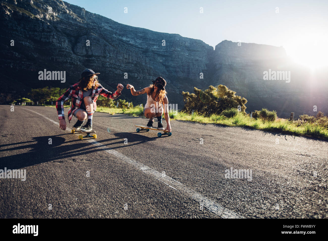 Best friends having fun with skateboard on open road. Young man and woman longboarding together on a sunny day. - Stock Image