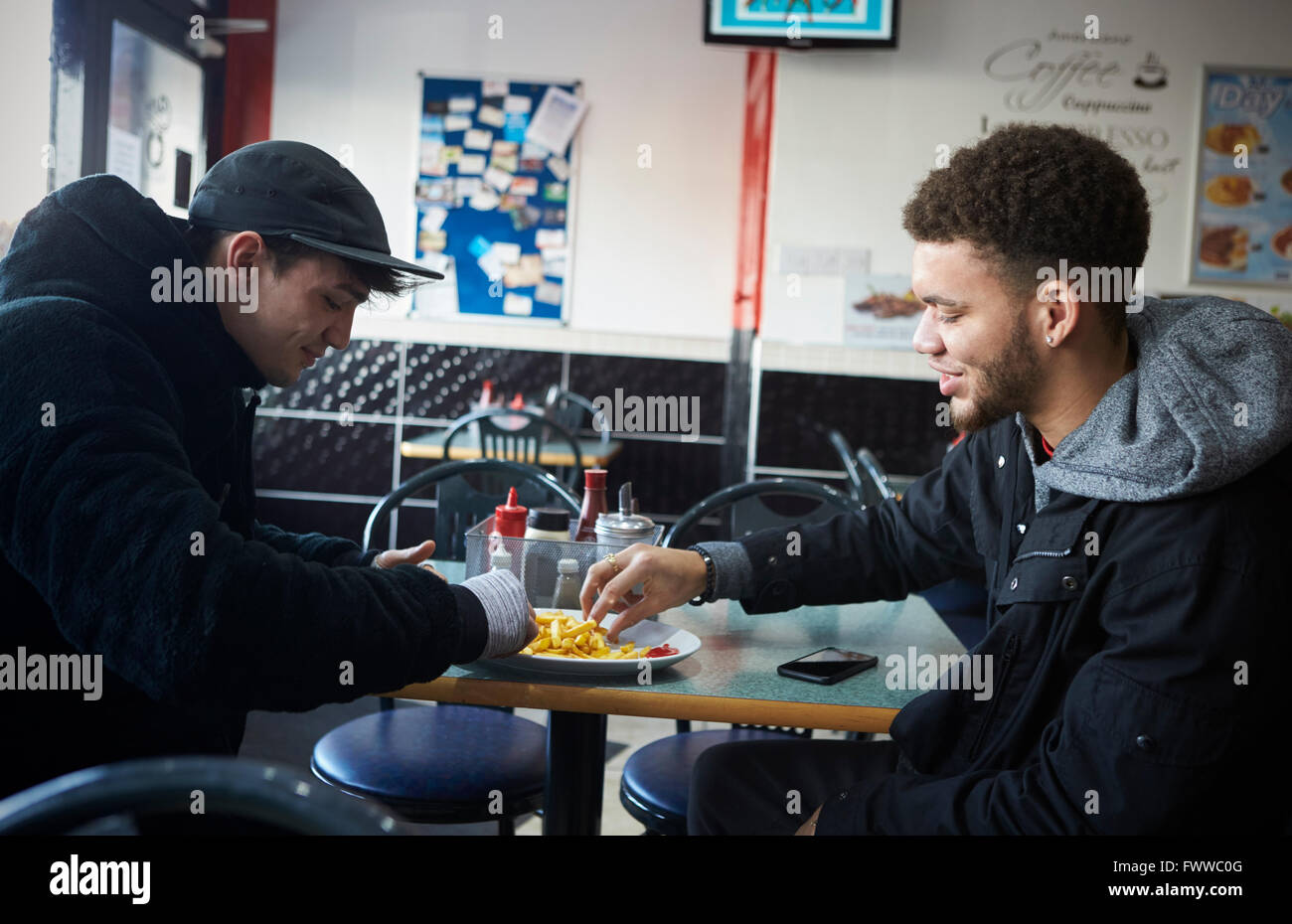 Two Male Students Eating Meal In Café Stock Photo