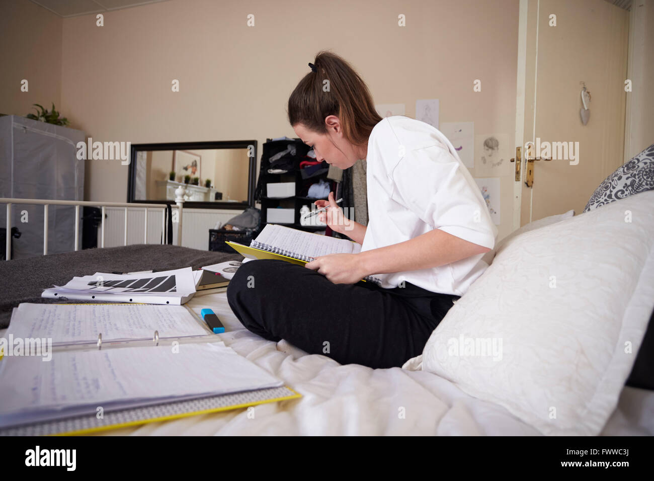 Female Student Working On Studies In Bedroom - Stock Image