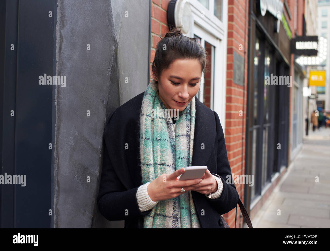Young Woman Reading Text Messaging On City Street - Stock Image