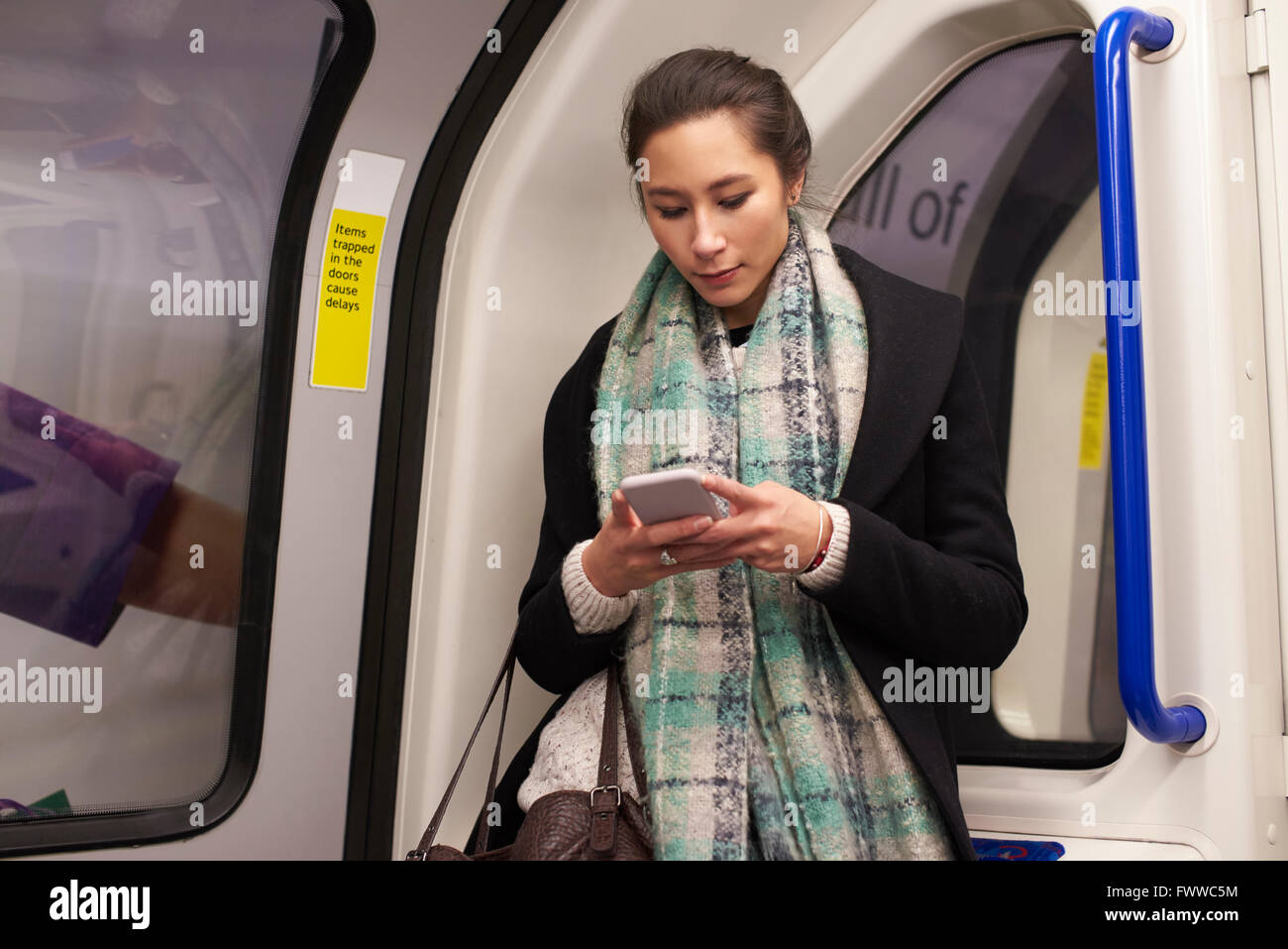 Woman Standing In Metro Carriage Looking At Text Message - Stock Image