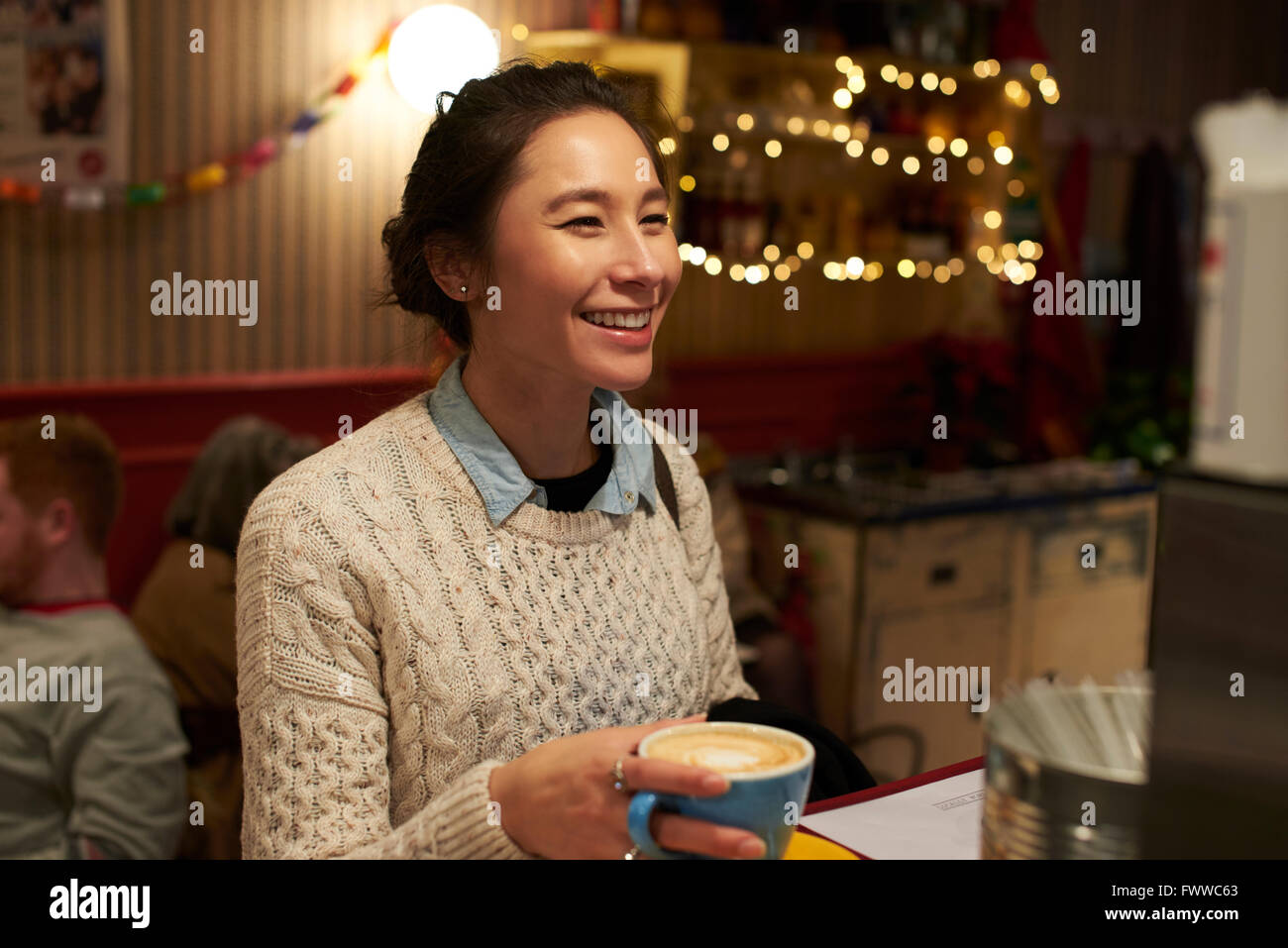 Evening Shot Of Young Woman Relaxing In Coffee Shop - Stock Image