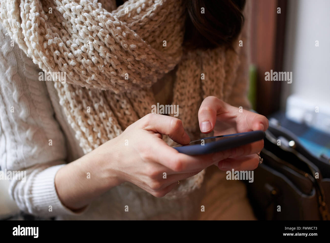 Close Up Of Young Woman Sending Text Message On Mobile Phone - Stock Image