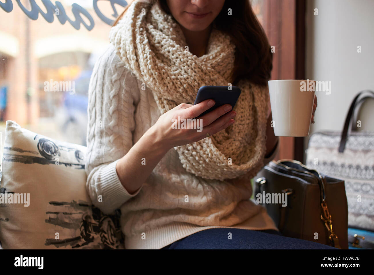 Young Woman Sitting In Coffee Shop Reading Text Message - Stock Image