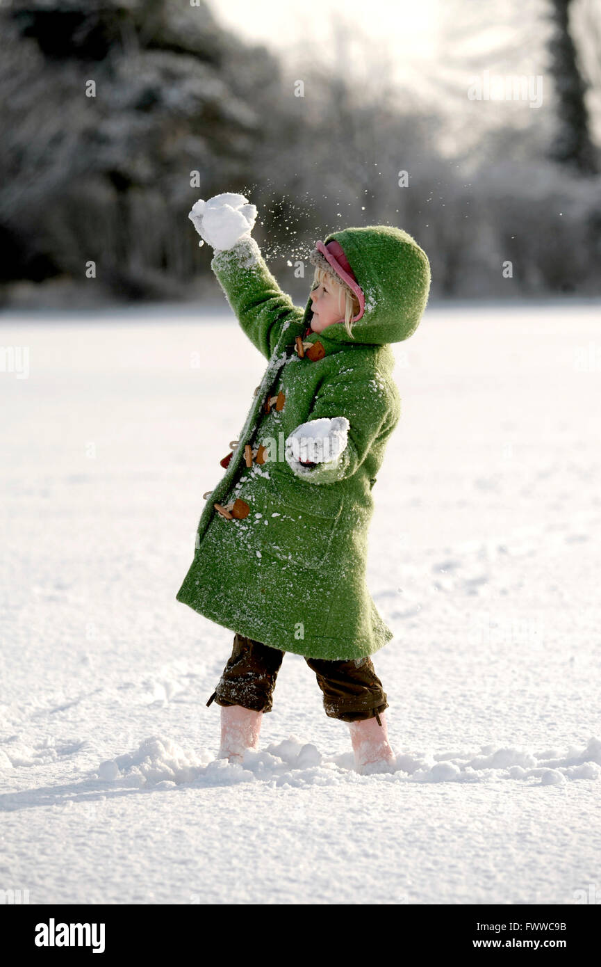 Child in green coat throwing a snowball - Stock Image