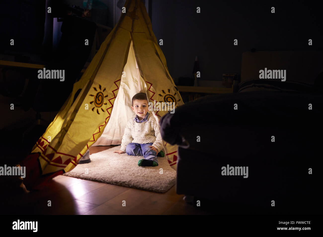 Young Boy Playing Inside Tent Set Up Indoors - Stock Image