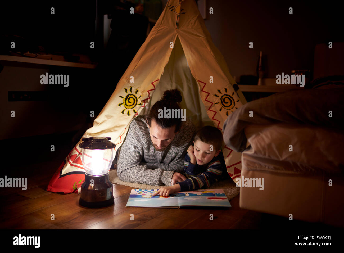 Father And Son Reading Inside Tent Set Up Indoors - Stock Image