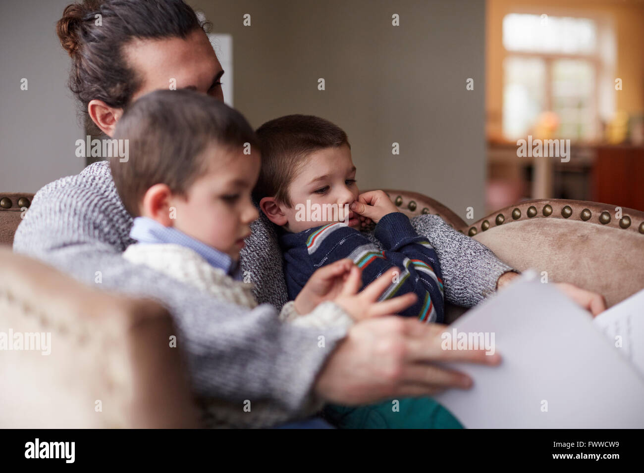 Father Sitting In Chair At Home Reading Story To Sons - Stock Image