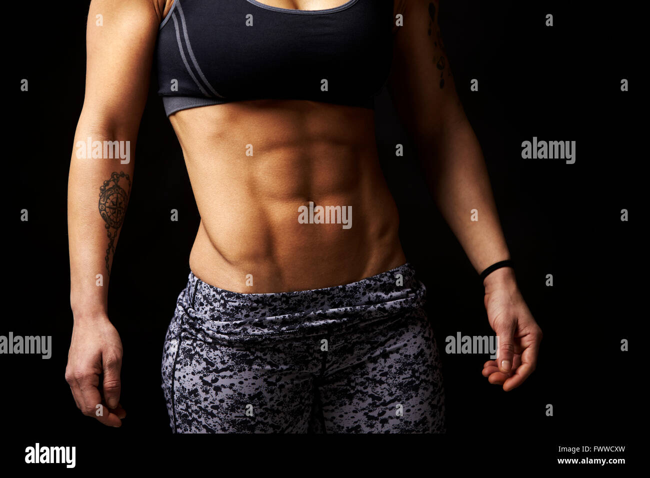 Mid-section crop shot of muscular young woman's abs and arms - Stock Image