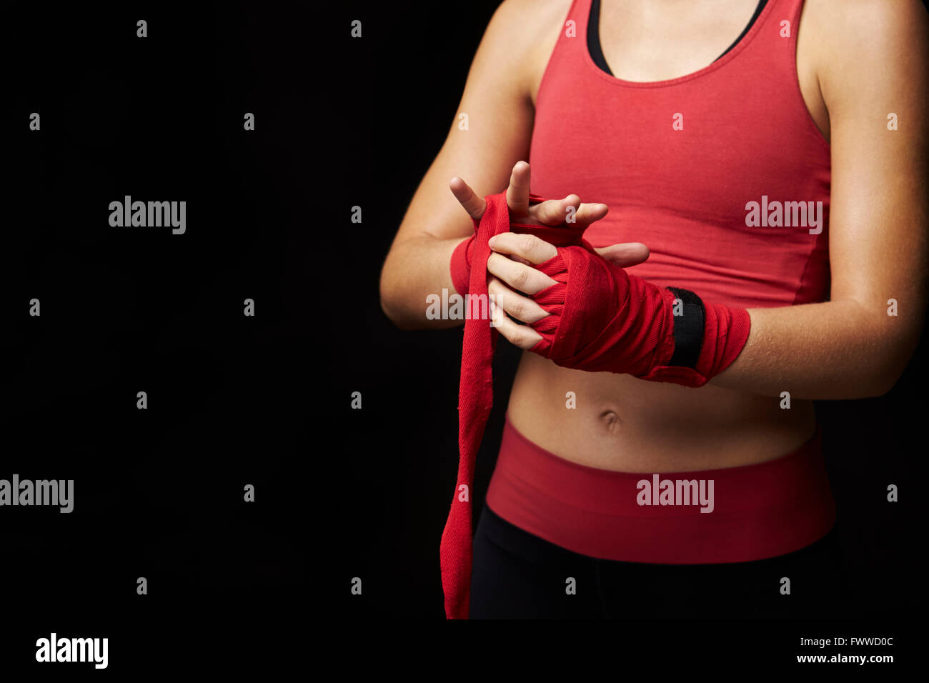 Mid-section of woman wrapping hand for boxing training - Stock Image