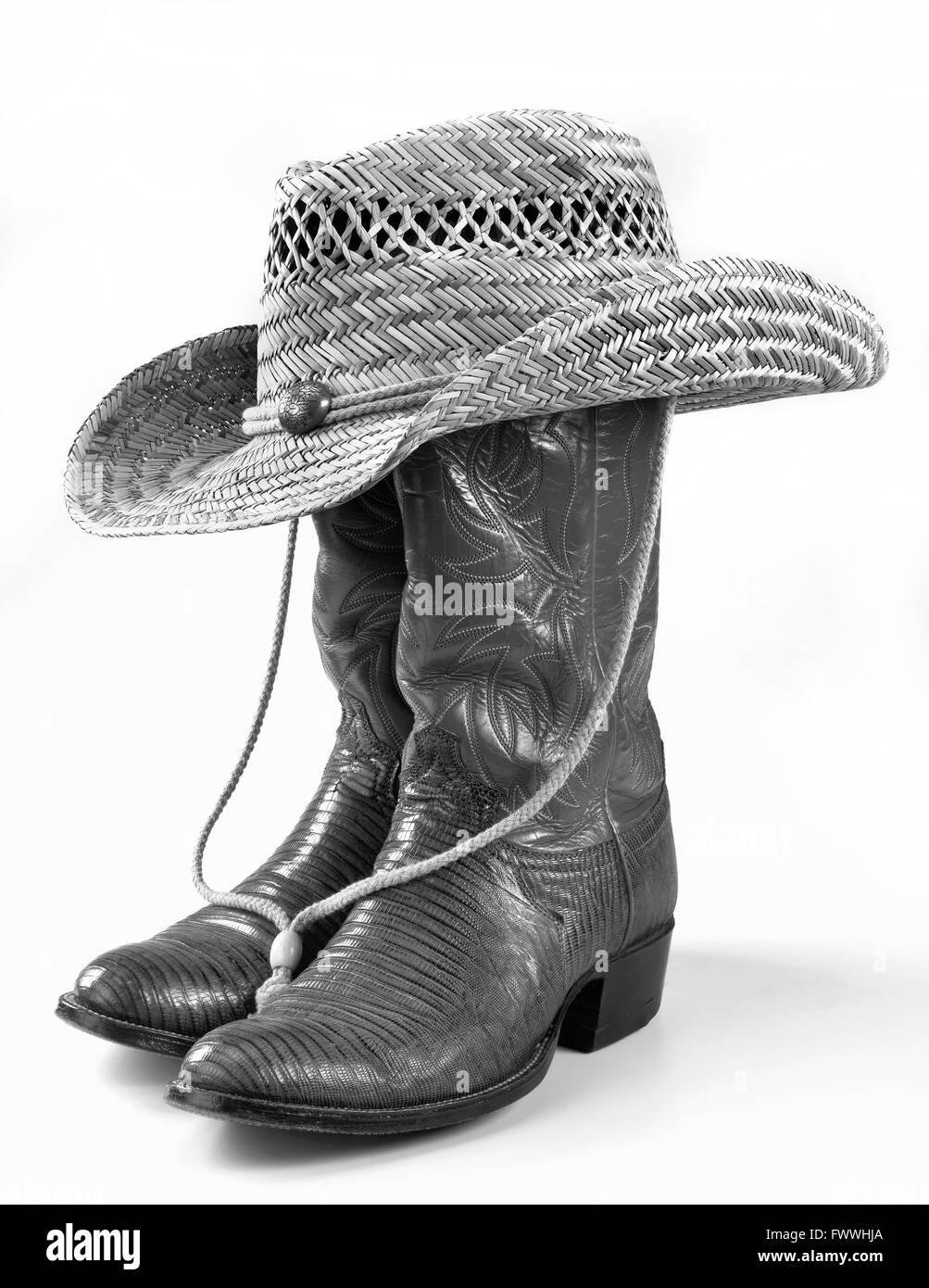 121fd27c4f5 Cowboy boots and straw hat in black and white. - Stock Image