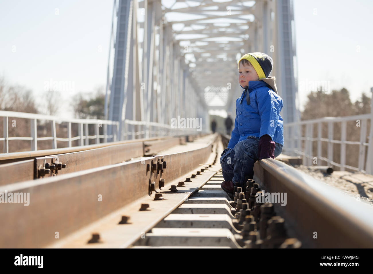 Portrait of a little boy sitting on the rails in the daytime. Belarus - Stock Image