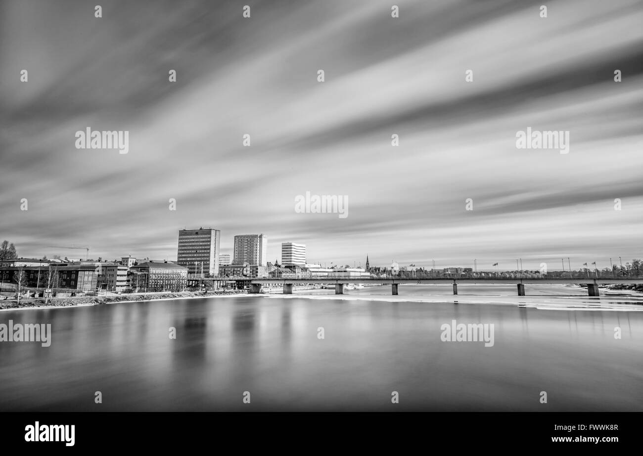 Downtown Umeå, Sweden with some ice in the river and clouds - Stock Image