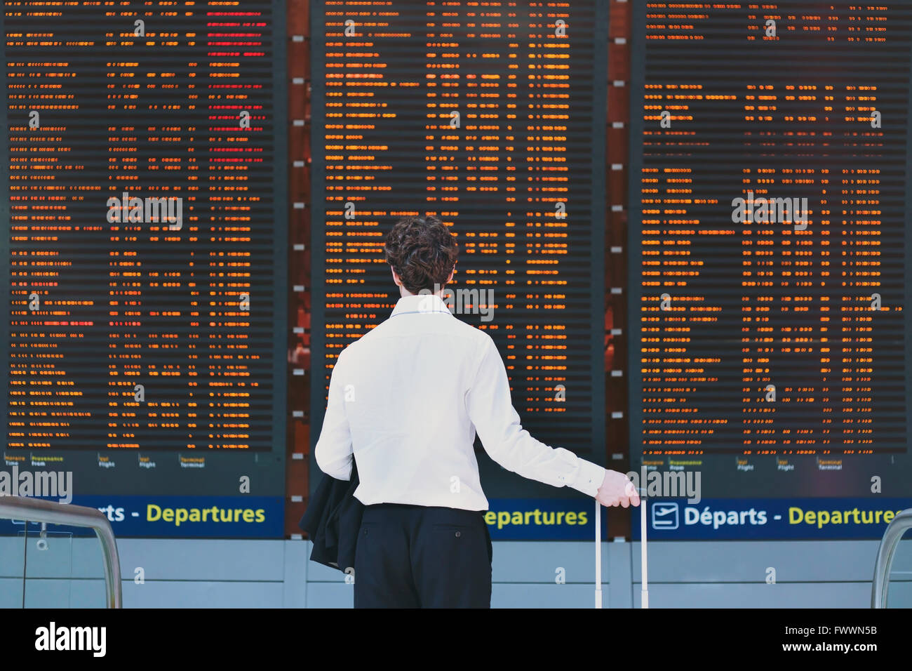people in the airport, business travel, passenger looking at timetable screen board - Stock Image