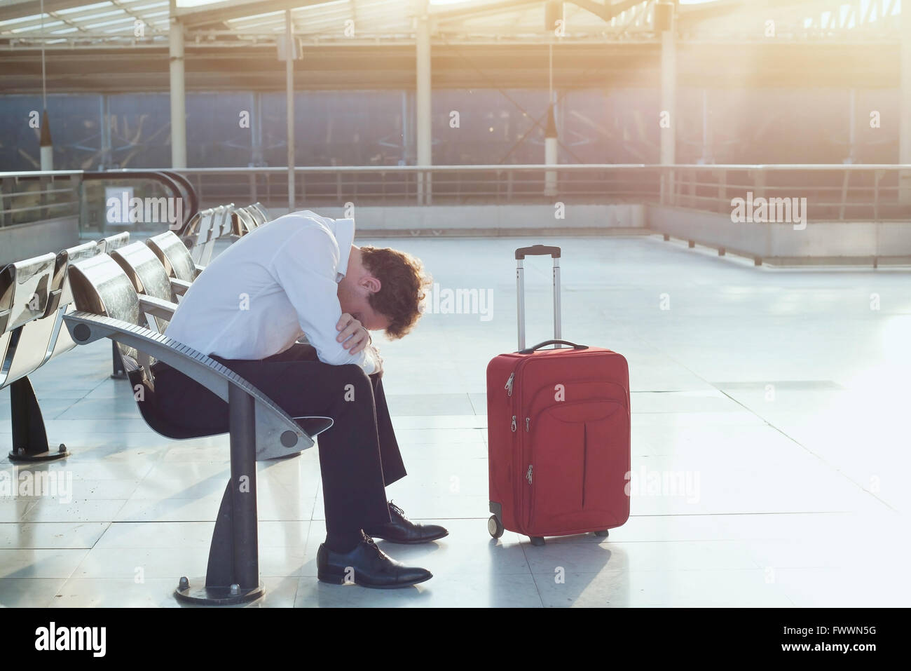 problem with transportation, delay of flight, depressed commuter with his luggage - Stock Image