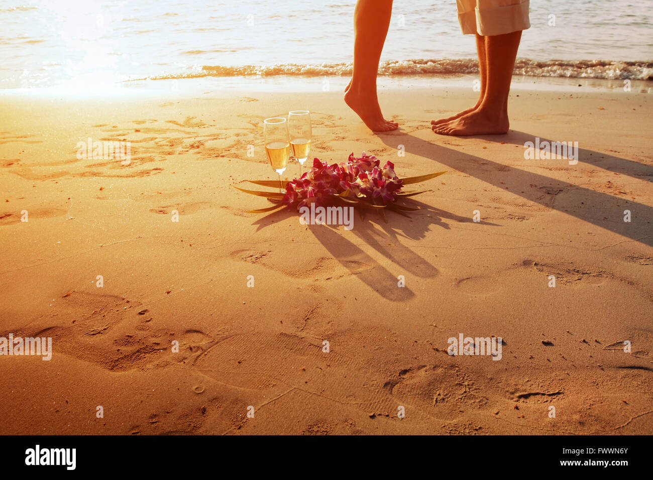wedding on the beach, feet of romantic couple and two glasses of champagne at sunset Stock Photo