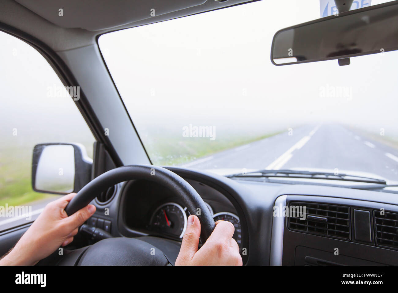 driving car in fog, bad weather conditions, road in foggy day with zero visibility - Stock Image
