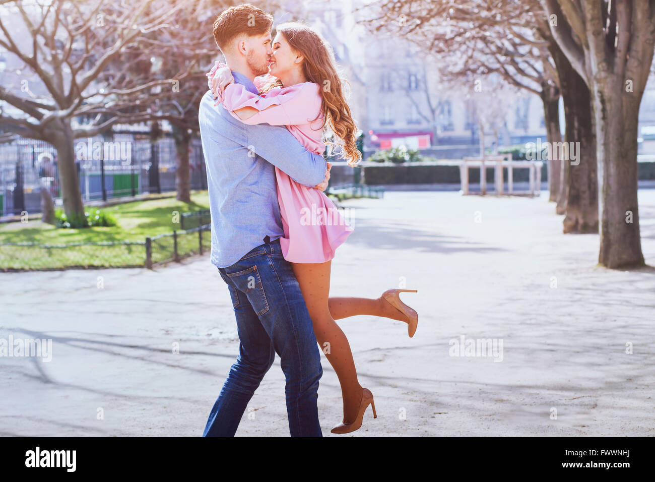 happy young beautiful couple kissing and smiling outdoors - Stock Image