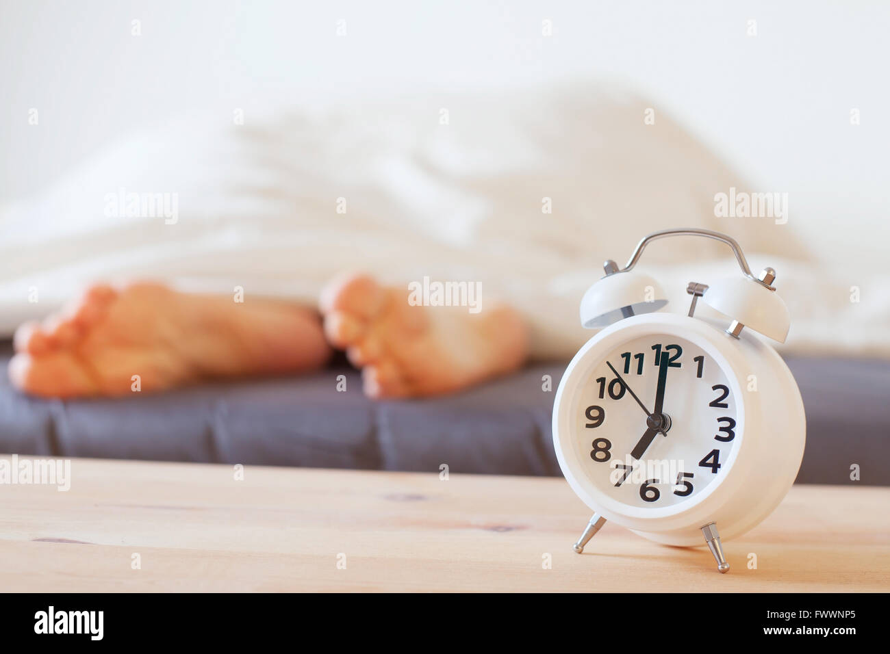 alarm clock and feet of sleeping person, morning concept, wake up - Stock Image