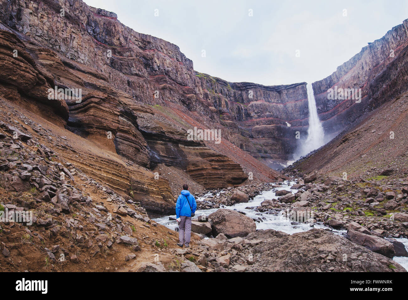 hiker walking to Hengifoss waterfall in Iceland, beautiful amazing landscape - Stock Image