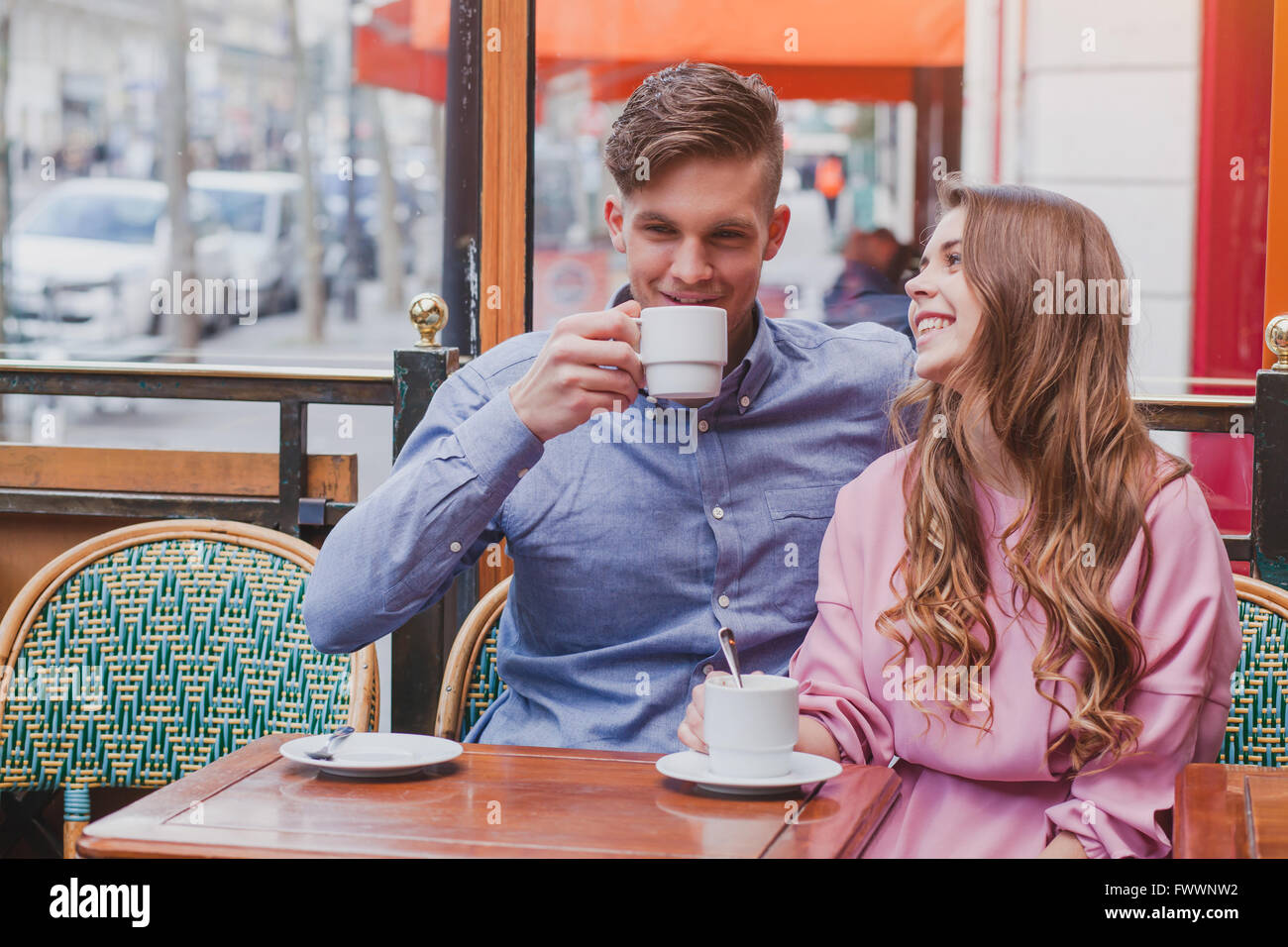 young happy couple drinking coffee and laughing in cafe in Europe, dating, good positive moments - Stock Image