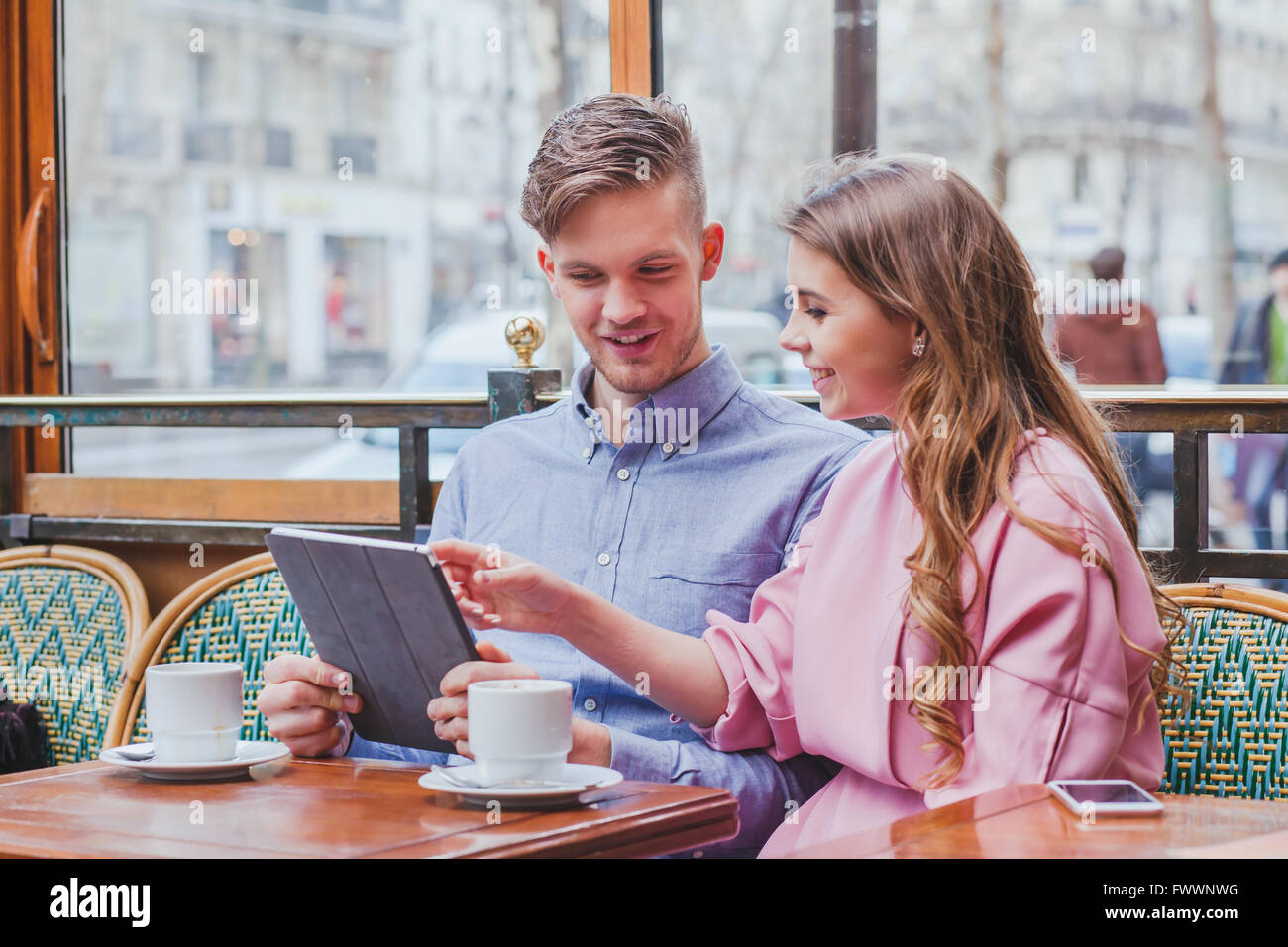 young couple with digital tablet in cafe, smiling happy man and woman looking to the screen, using internet, buy - Stock Image