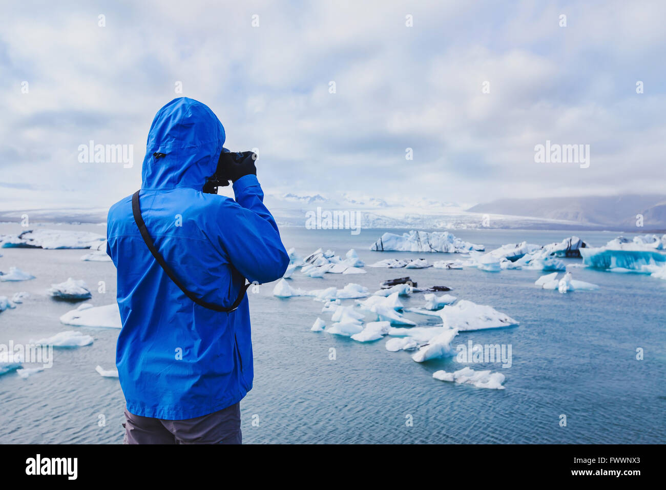 nature travel photographer, person taking photo of arctic icebergs in Iceland - Stock Image