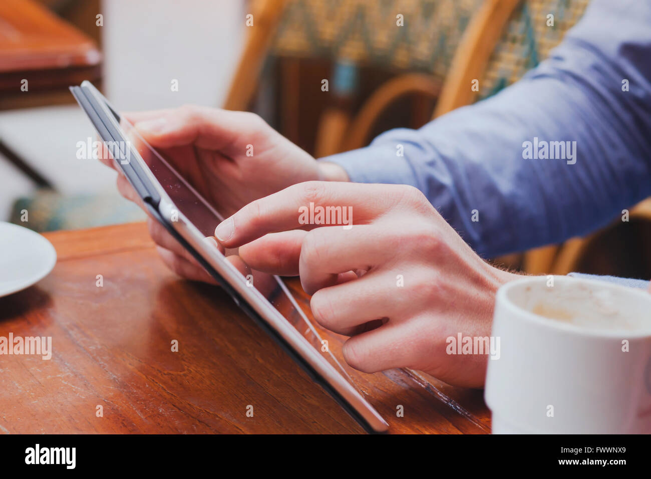 checking email on touchpad, close up of hands using digital tablet in cafe - Stock Image