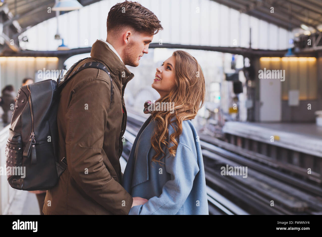 long distance relationship, couple on platform at the train station, meeting or parting concept - Stock Image