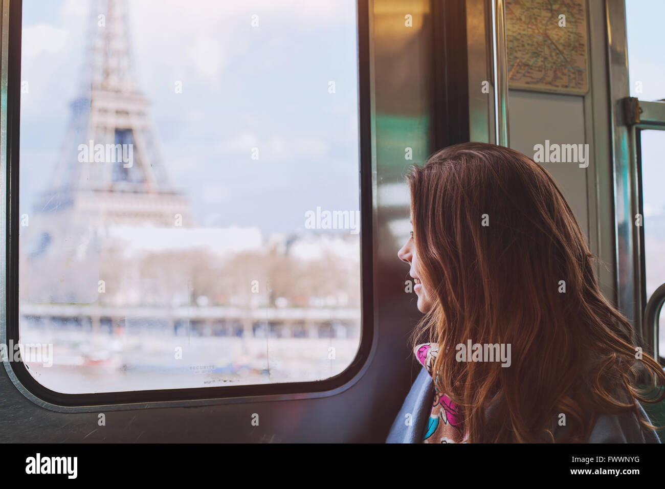 tourist looking to the Eiffel Tower through the window of metro in Paris, smiling girl visiting France Stock Photo