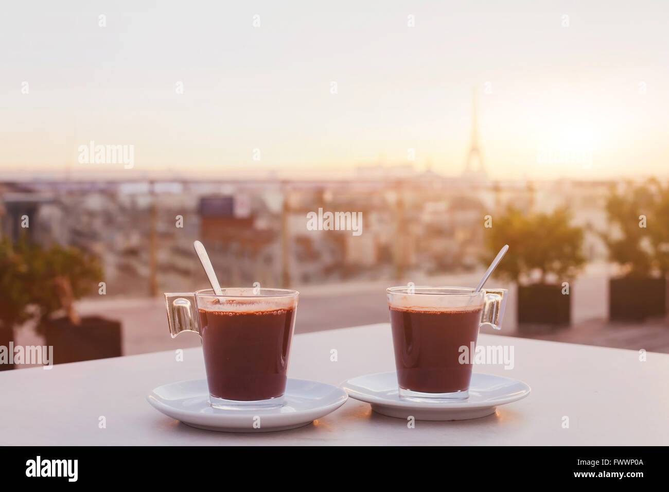 two cups of coffee or hot chocolate and Paris skyline at sunset, cafe with panoramic view of the city with Eiffel - Stock Image