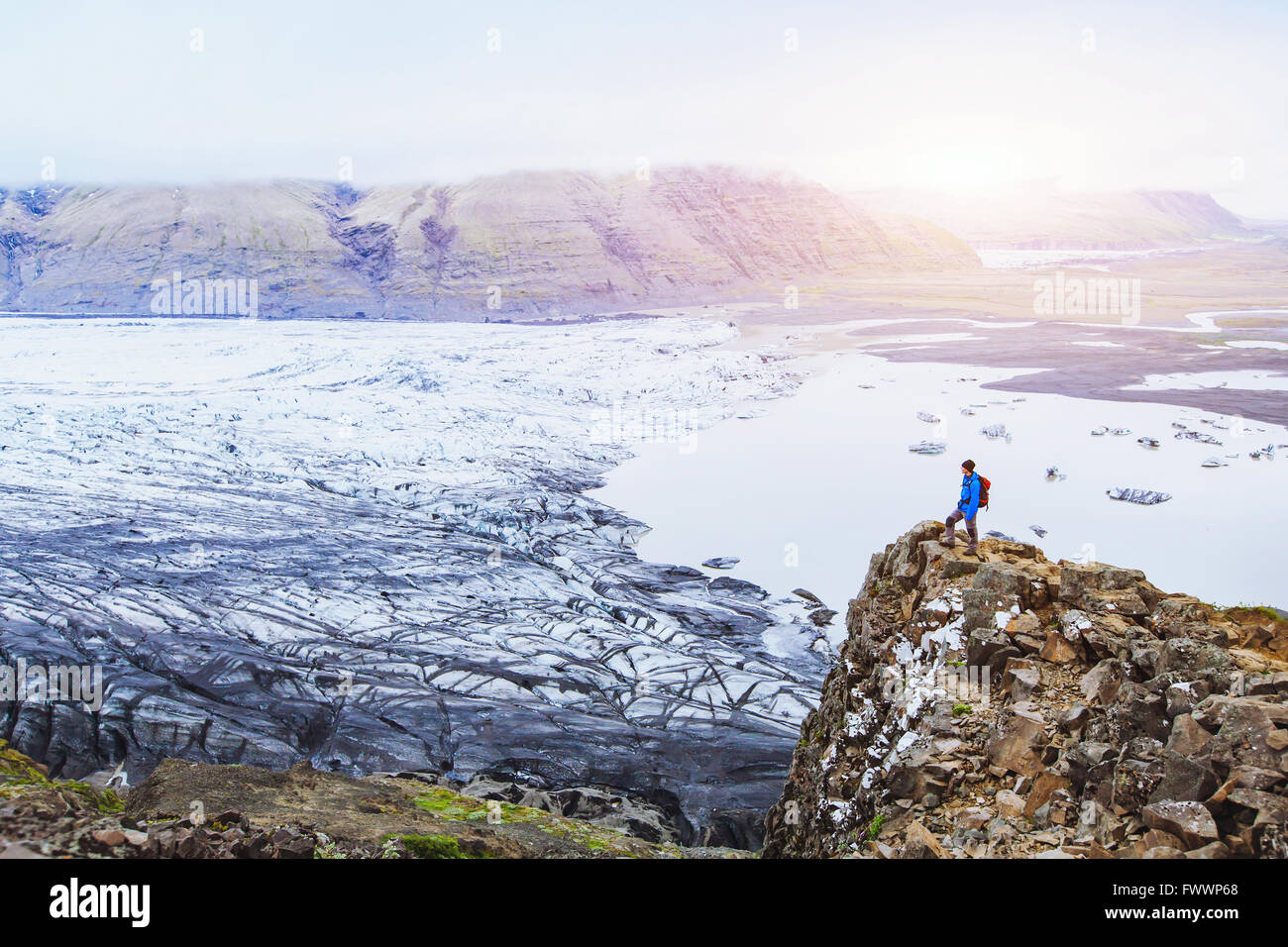 hiking in winter, backpacker enjoying panoramic landscape of glacier in Iceland at sunset in national park Skaftafell - Stock Image