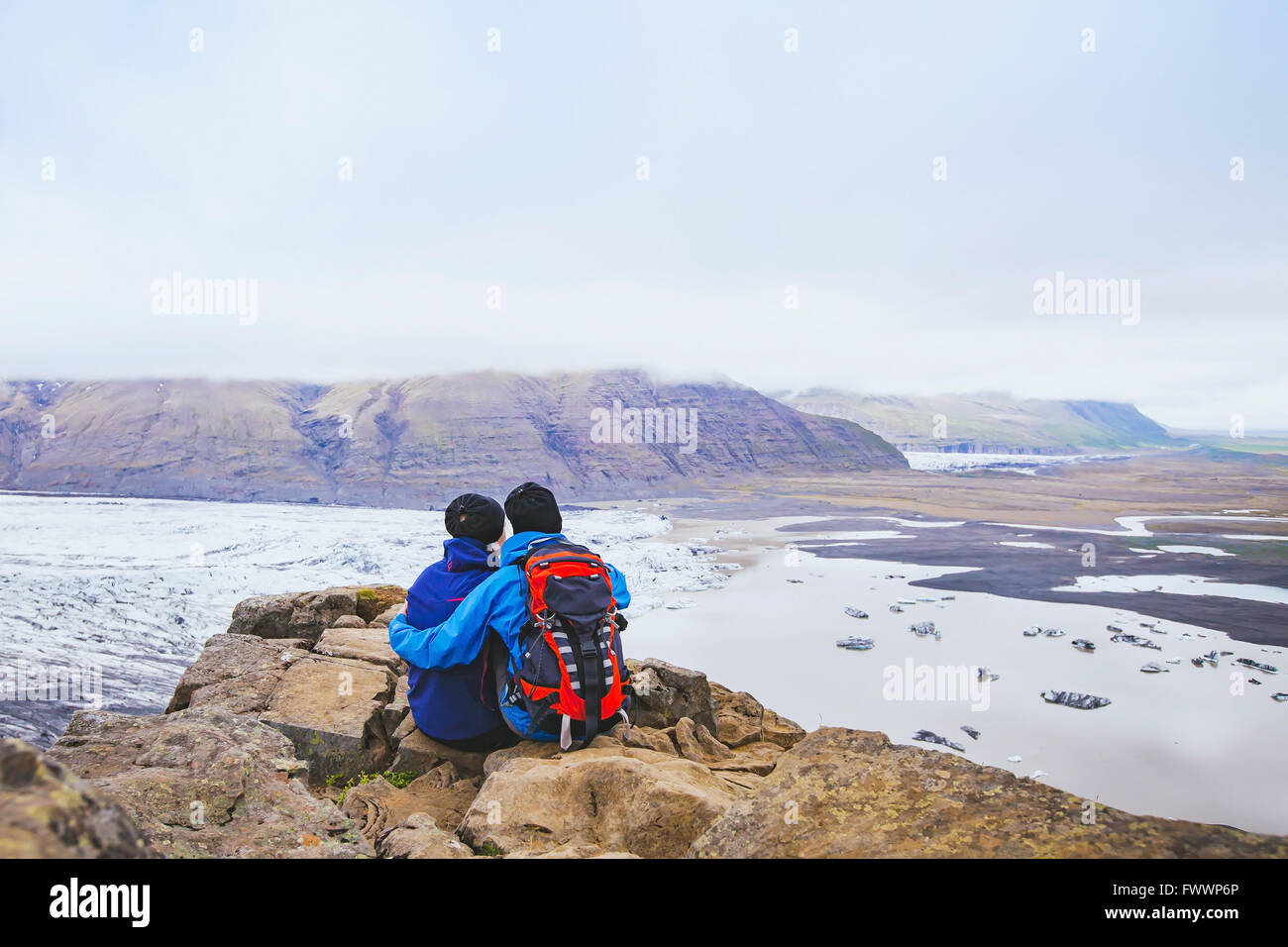 couple of hikers travel in Iceland, two backpackers enjoying view of glacier and mountain landscape Stock Photo
