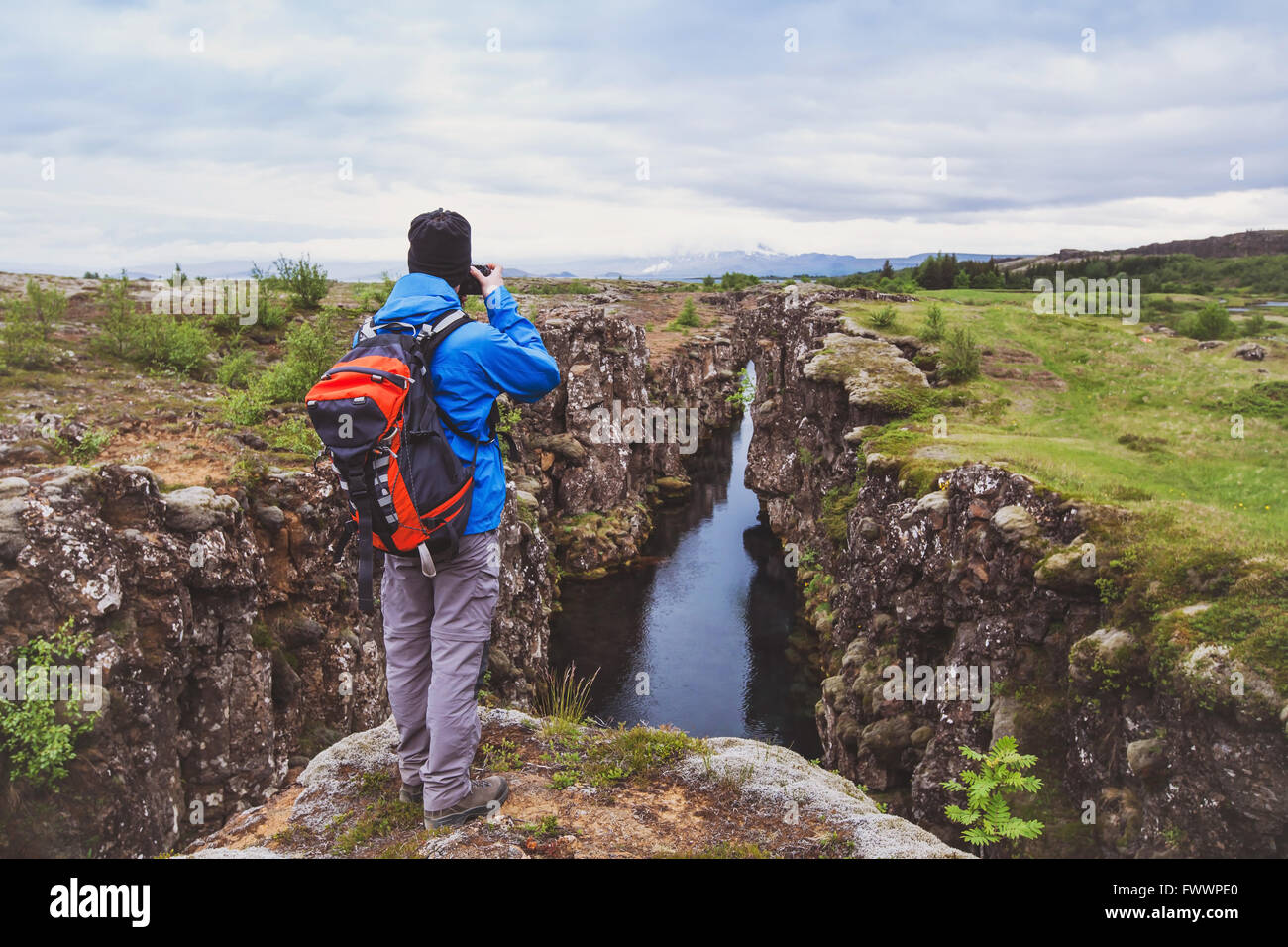 nature photographer, hiker with backpack taking photo of beautiful landscape in Iceland national park Thingvellir - Stock Image