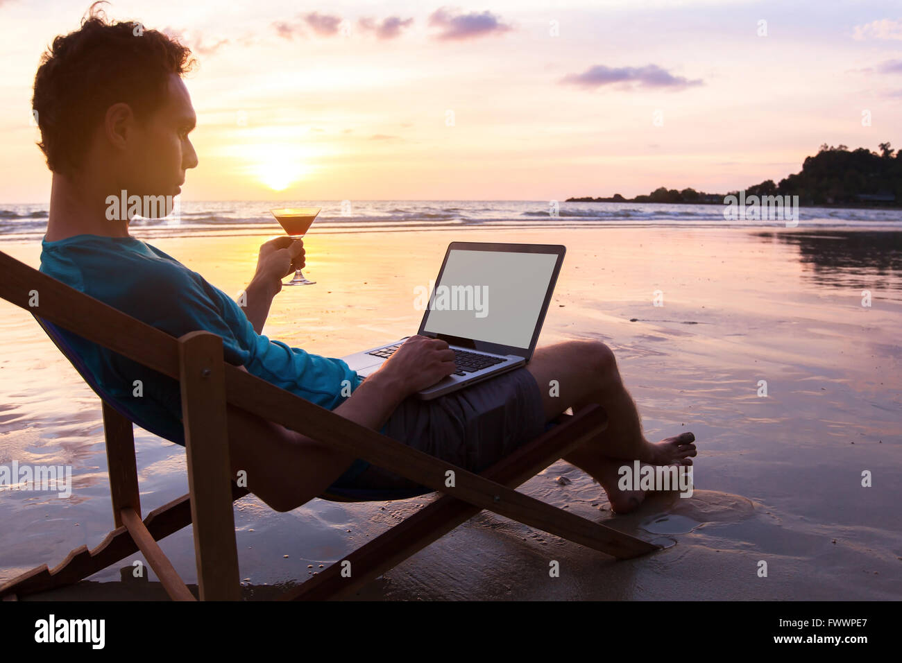 young business man with cocktail working on laptop on the beach at sunset, freelance job online, focus on the screen - Stock Image