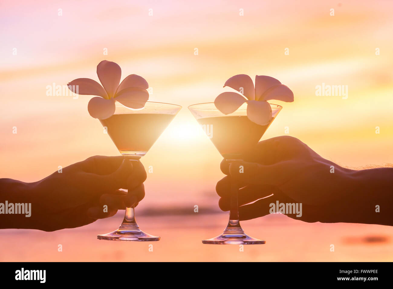 tropical cocktails on the beach, couple of hands with glasses - Stock Image