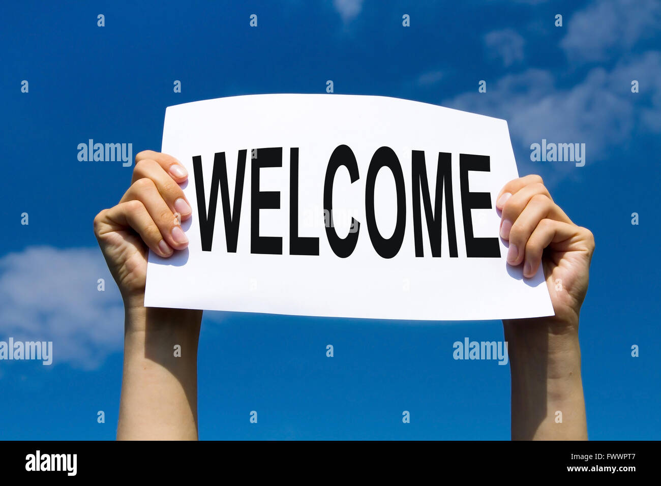 welcome concept, hands holding paper sign on blue sky - Stock Image