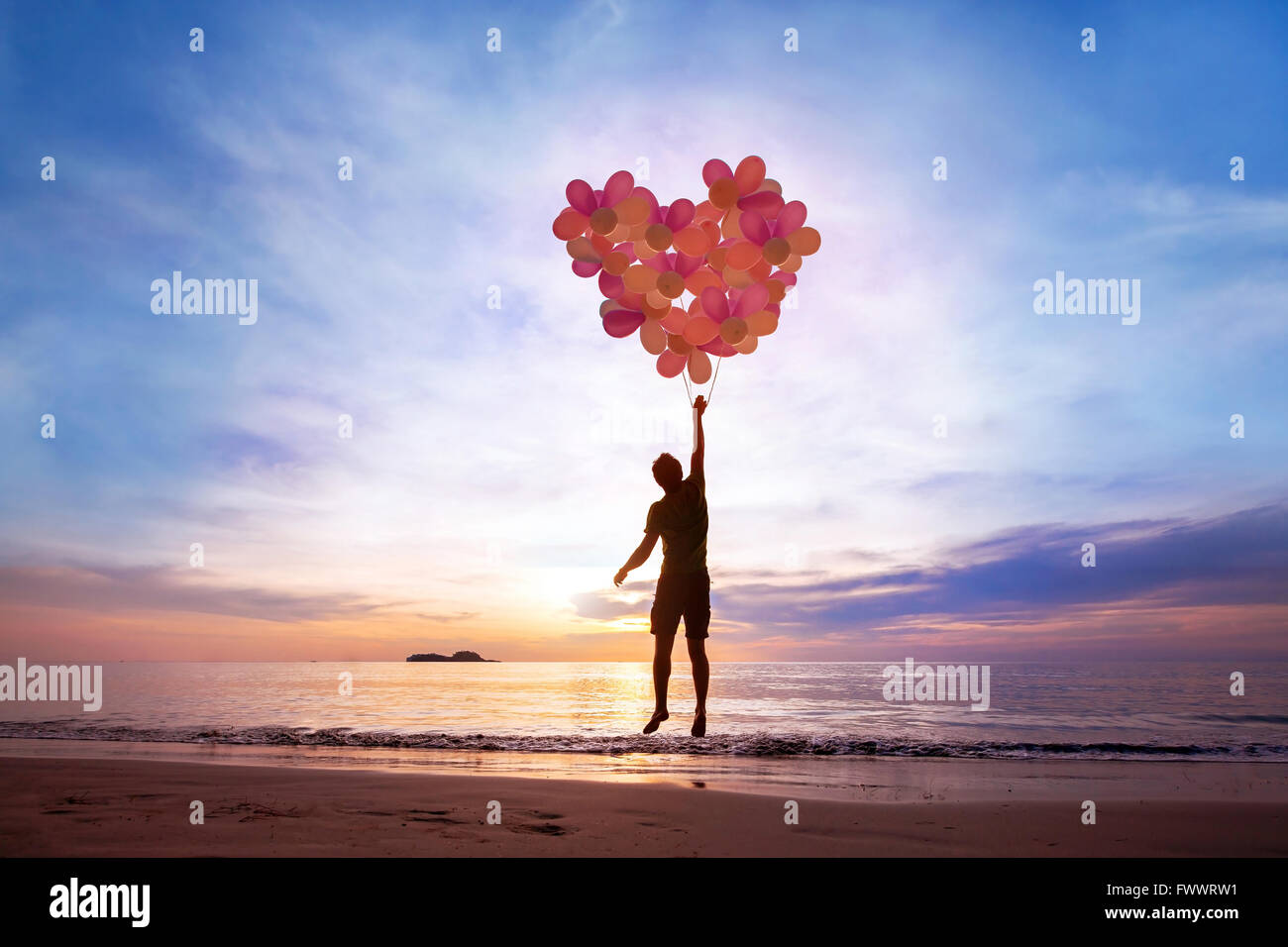 love concept, man flying with heart from balloons, fall in love - Stock Image