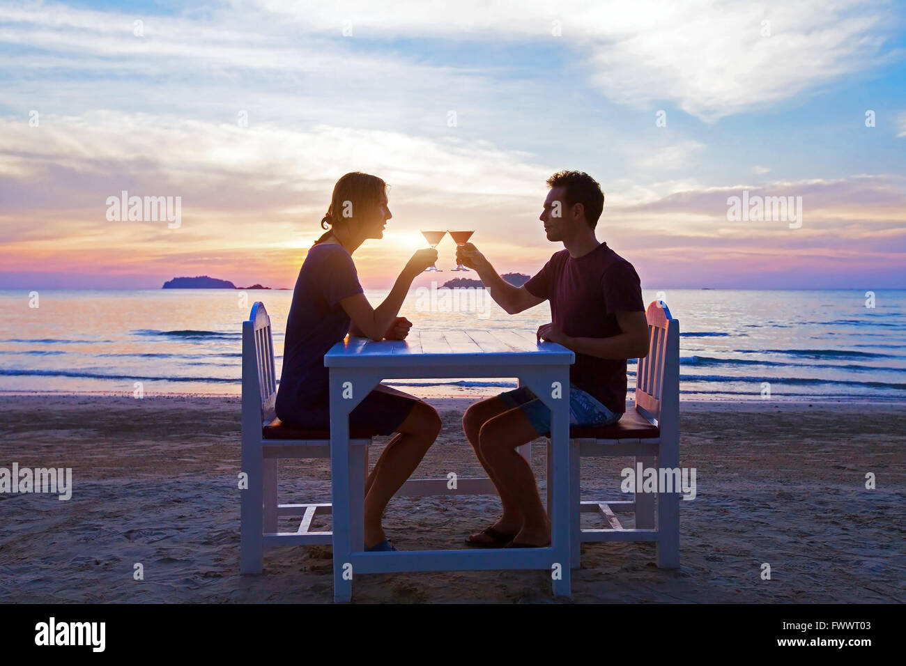 romantic dinner on the beach in luxury restaurant, couple on honeymoon drinking tropical cocktails at sunset - Stock Image