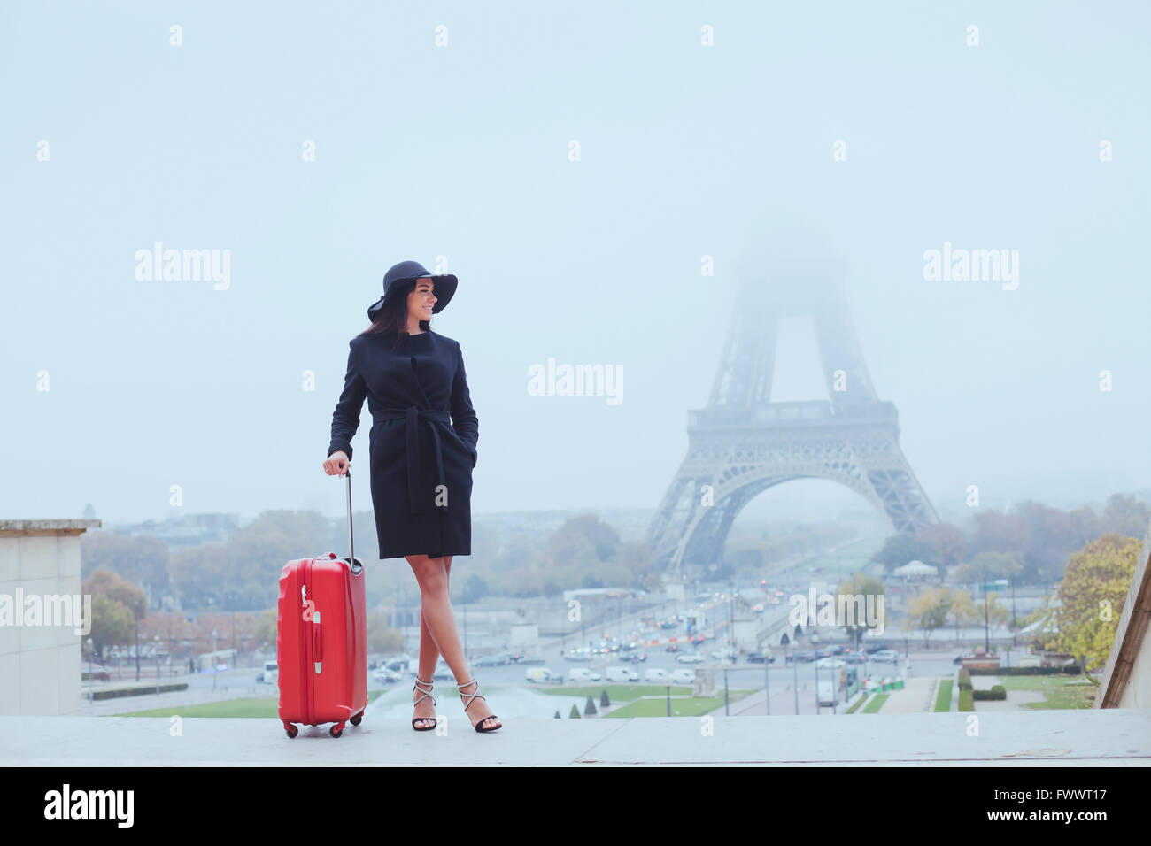 tourist in Paris, Europe tour, woman with luggage near Eiffel Tower, France - Stock Image