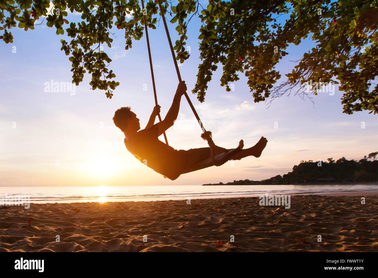 swing on paradise tropical beach at sunset, happy people enjoying summer - Stock Image