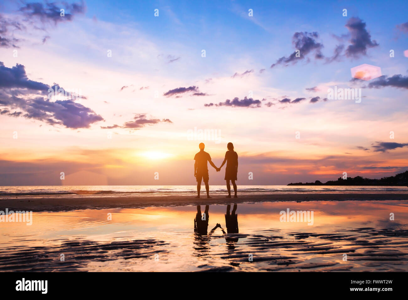 romantic couple on the beach at sunset, silhouettes of man and woman together - Stock Image