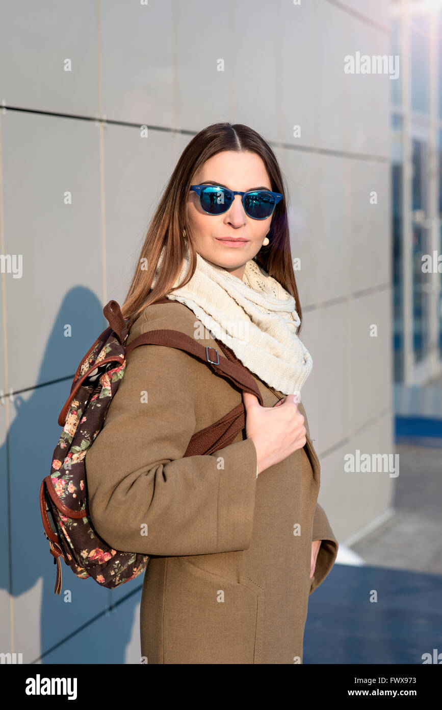 Fashion girl standing in glasses and a beige coat with backpack looks - Stock Image