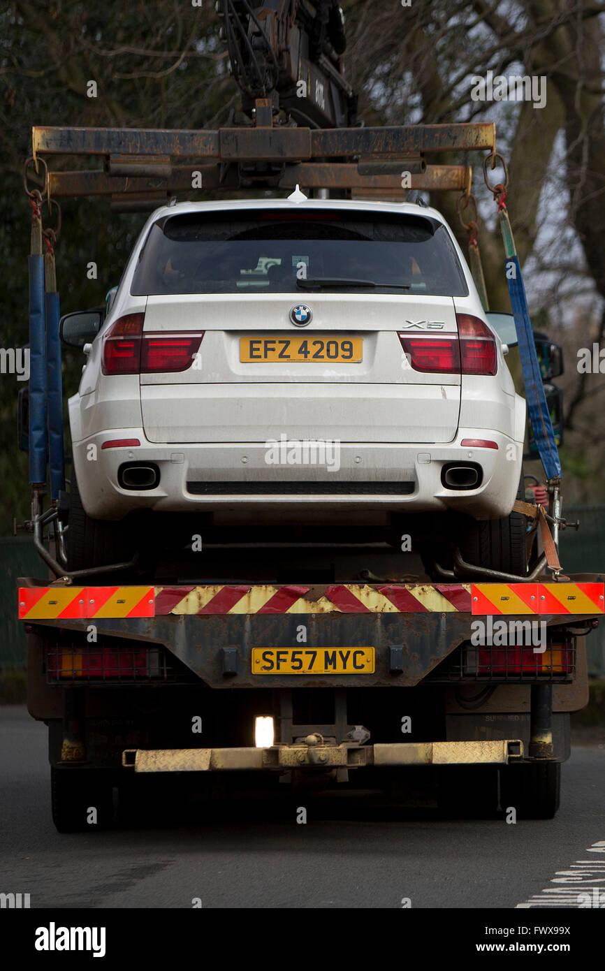 An illegally parked BMW X5 4x4 car being removed by parking wardens on a flatbed truck - Stock Image