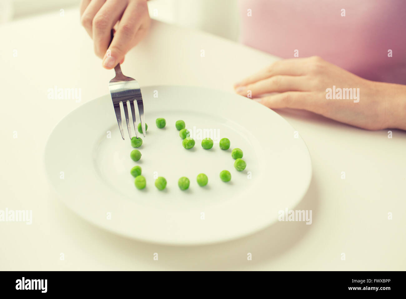 close up of woman with fork eating peas - Stock Image