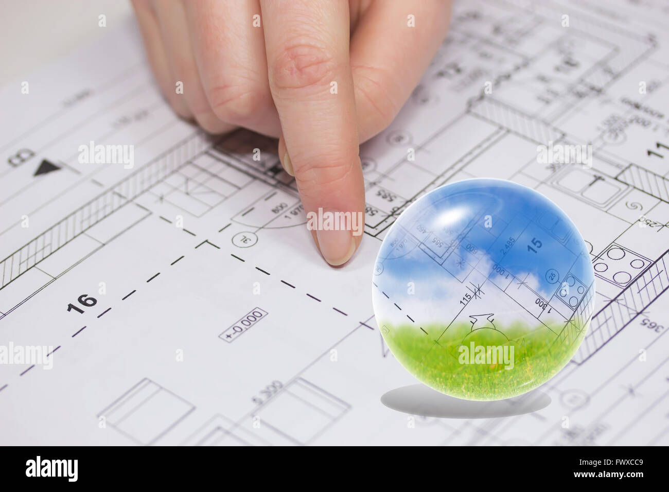 Finger from an unknown person is showing at the plan of the house finger from an unknown person is showing at the plan of the house blue sky blueprint and green grass are in the glass ball malvernweather Choice Image