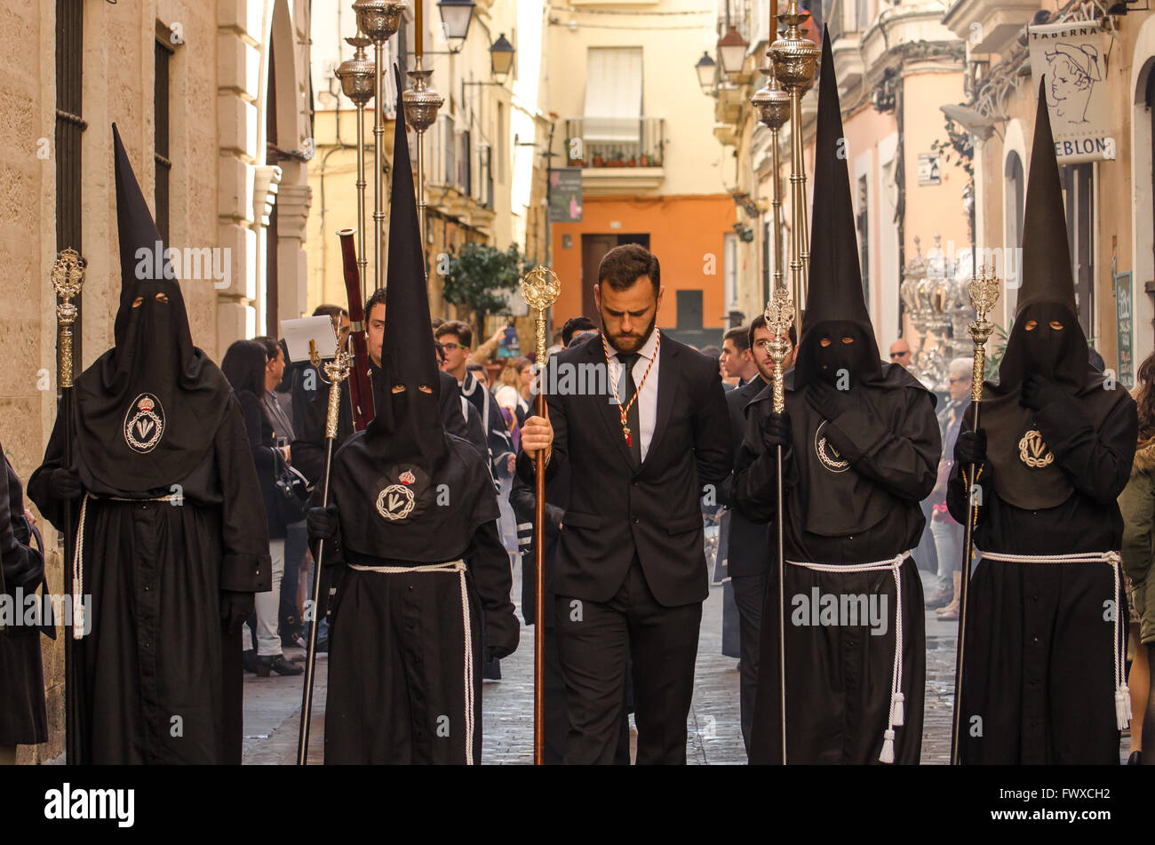 Hooded Penitents heads bowed during Semana Santa processions Cadiz City 2016 - Stock Image
